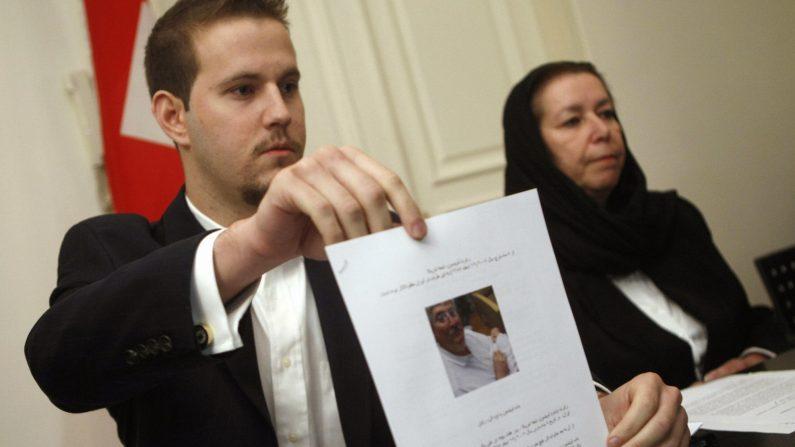 El estadounidense Daniel Levinson (izq.) muestra una foto de su padre, el exagente del FBI Robert Levinson, sosteniendo a su nieto Ryan durante una conferencia de prensa con su madre Christine en la embajada de Suiza en Teherán, el 22 de diciembre de 2007. (BEHROUZ MEHRI/AFP a través de Getty Images)
