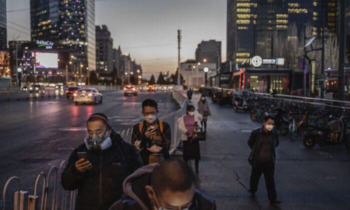 Los viajeros chinos llevan máscaras protectoras mientras hacen cola para esperar un autobús, en Beijing, el 20 de marzo de 2020. (Kevin Frayer/Getty Images)