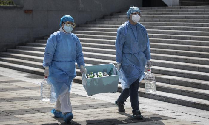 Trabajadores médicos llevan una caja en Wuhan, provincia de Hubei, China, el 10 de marzo de 2020. (Stringer/Getty Images)