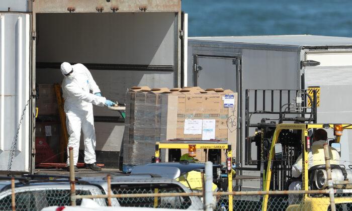 Trabajadores descargan suministros de un camión con equipo de protección para ser cargados en el MSC Magnifica atracado en la Terminal de Pasajeros de Fremantle en Fremantle, Australia, el 24 de marzo de 2020. (Paul Kane/Getty Images)