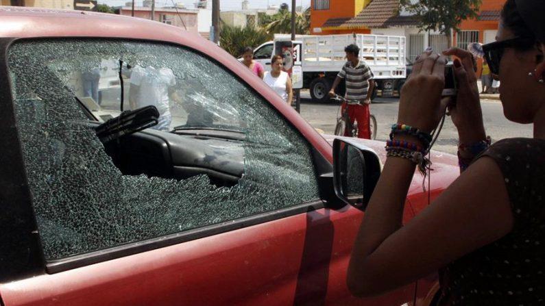 Un joven toma una fotografía el martes 19 de abril de 2011, de uno de los vehículos afectados en Veracruz, México, después de que diez presuntos narcotraficantes murieran y diez más fueran detenidos tras un enfrentamiento con soldados mexicanos, según informaron fuentes oficiales. EFE/Saul Ramirez/Archivo