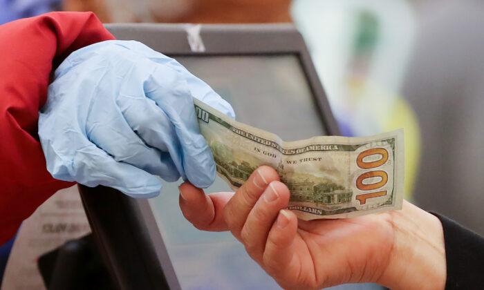 Una mujer paga en efectivo mientras usa guantes durante el horario especial abierto sólo para personas mayores y discapacitadas en el Northgate Gonzalez Market, un supermercado especializado para hispanos, en Los Ángeles, California, el 19 de marzo de 2020. (Mario Tama/Getty Images)