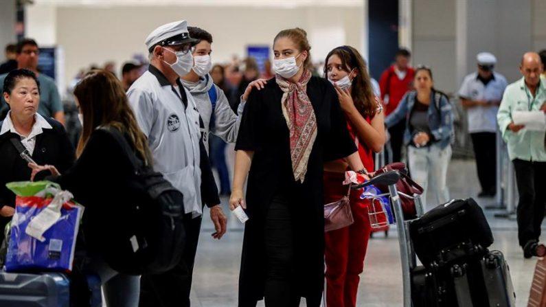 Pasajeros usan máscaras como precaución contra la propagación del nuevo coronavirus COVID-19 durante su llegada, este jueves, al Aeropuerto Internacional de Sao Paulo (Brasil). EFE/ Sebastião Moreira