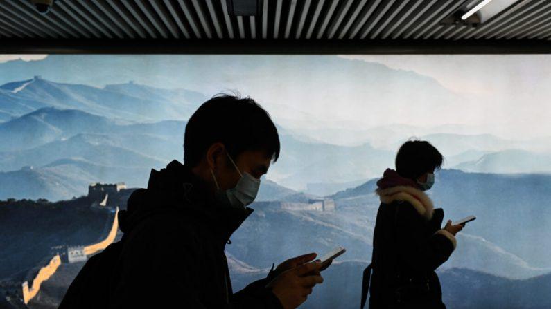 Un hombre y una mujer con máscaras usan su teléfono móvil mientras caminan en una estación de metro en Beijing el 11 de marzo de 2020. (Wang Zhao/AFP a través de Getty Images)
