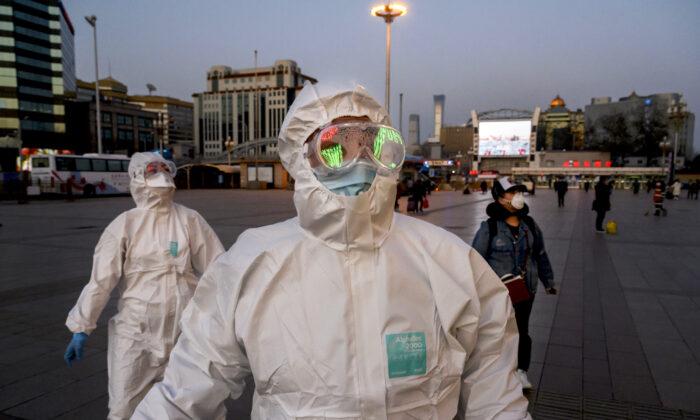 Personas usan máscaras faciales y trajes protectores cuando llegan a la estación de tren de Beijing el 13 de marzo de 2020. (Kevin Frayer / Getty Images)