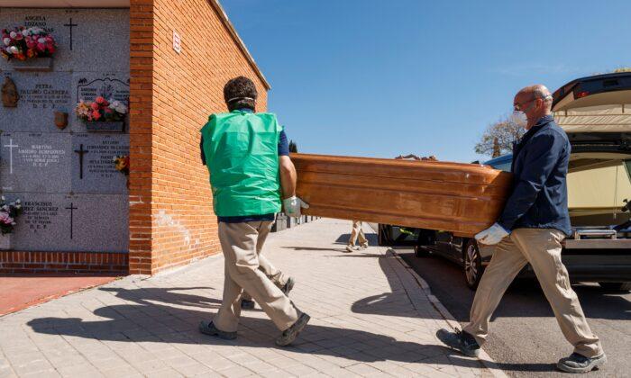 Empleados de una funeraria con máscaras llevan el ataúd de una víctima de COVID-19 durante un entierro en el cementerio de Fuencarral en Madrid el 29 de marzo de 2020. (Baldesca Samper/AFP vía Getty Images)