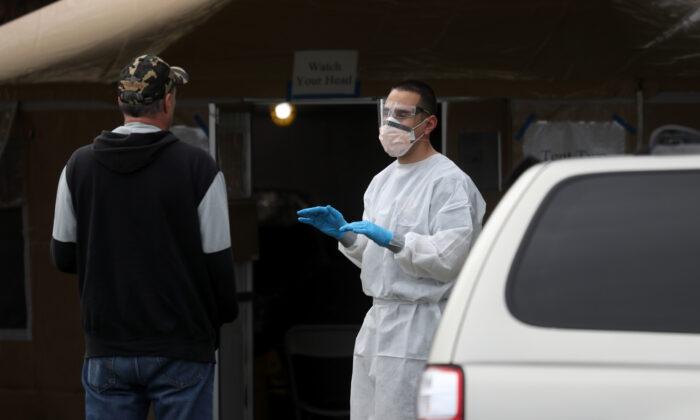 Un bombero revisa a un hombre que espera en fila para tomarse la prueba de COVID-19 en una estación pública de pruebas gratuita en Hayward, California, el 24 de marzo de 2020. (Justin Sullivan/Getty Images)