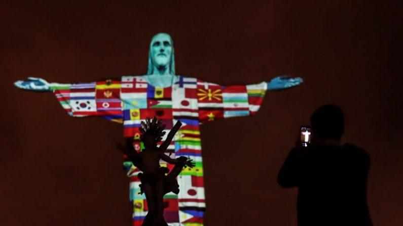 Las banderas de los países afectados por el virus del PCCh son proyectadas en la estatua de Cristo Redentor este miércoles, durante un acto de apoyo para los 166 países con casos de coronavirus, en Río de Janeiro (Brasil). EFE/Antonio Lacerda