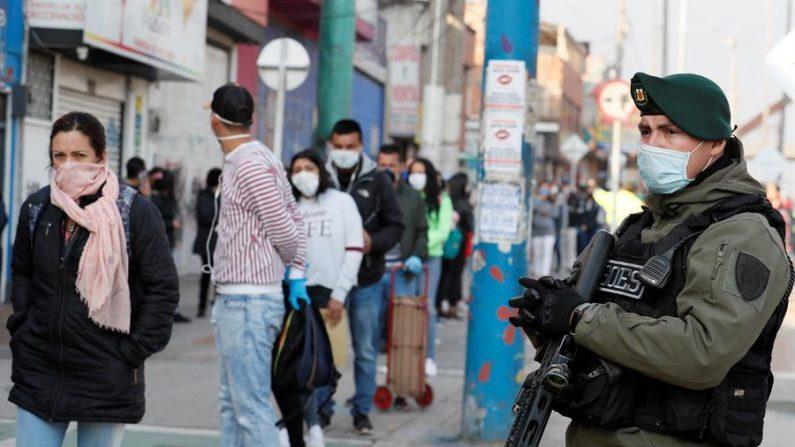 Un integrante de la policía con tapabocas custodia las filas formadas por decenas de personas que intentan abordar buses en las estaciones de transporte en una ciudad de Colombia. EFE/Carlos Ortega