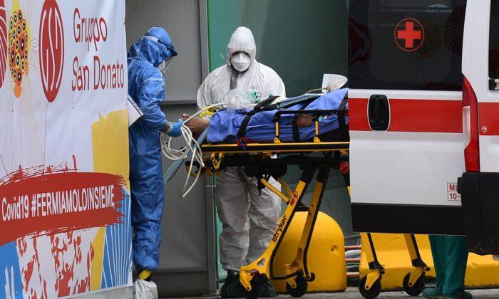 Trabajadores médicos trasladan a un paciente desde una ambulancia de la Cruz Roja Italiana a una unidad de cuidados intensivos establecida en un centro de deportes fuera del hospital San Raffaele en Milán, el 23 de marzo de 2020. (Miguel Medina/AFP via Getty Images)