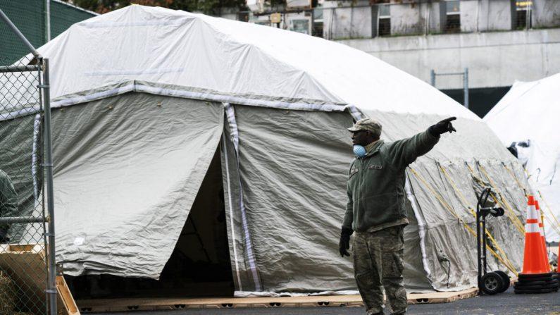 Un miembro de la Fuerza Aérea da instrucciones mientras trabajadores y miembros de la Guardia Nacional construyen una morgue improvisada en las afueras del Hospital Bellevue en la ciudad de Nueva York el 25 de marzo de 2020.  (Eduardo Muñoz Álvarez/Getty Images)
