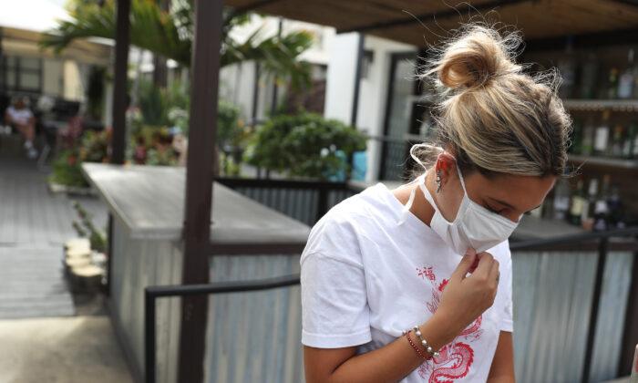 Pia Rodríguez espera un autobús cuando sale del hotel Beach Plaza para ir a otro hotel en Miami en Miami Beach, Florida, el 23 de marzo de 2020. (Joe Raedle / Getty Images)