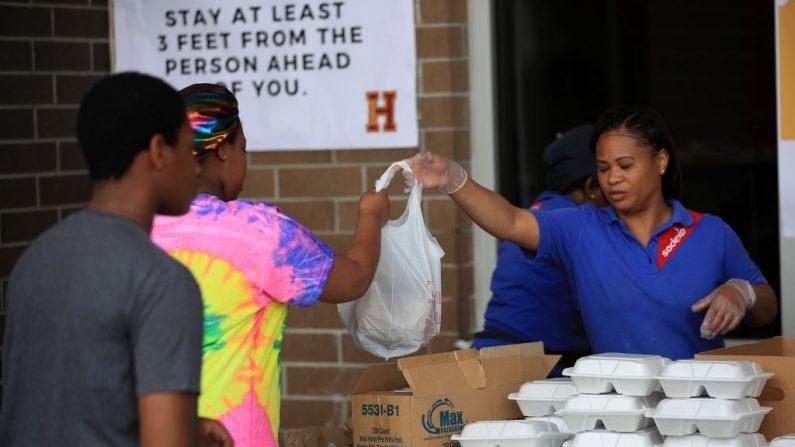 La escuela Paul Habans Charter reparte suministros, incluyendo comida, libros y computadoras a los estudiantes y a la comunidad mientras las escuelas de Louisiana cierran por un mes debido a la propagación del coronavirus (COVID-19) el 17 de marzo de 2020 en Nueva Orleans, Louisiana. (Chris Graythen/Getty Images)