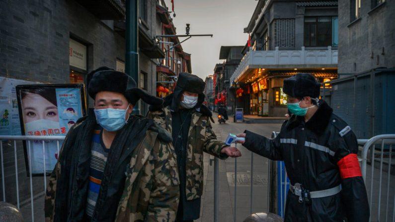 Un hombre chino usa una máscara protectora mientras él y otros hacen que un guardia controle su temperatura en una entrada temporal a un área comercial en Beijing el 11 de marzo de 2020. (Kevin Frayer/Getty Images)