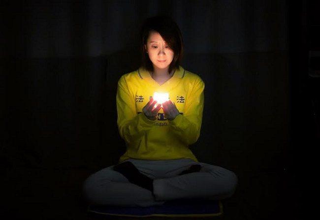 Una mujer de Nueva York participa en la vigilia con velas online para conmemorar la persecución de los practicantes de Falun Gong en China, el 23 de abril de 2020. (Cortesía del Centro Tuidang)