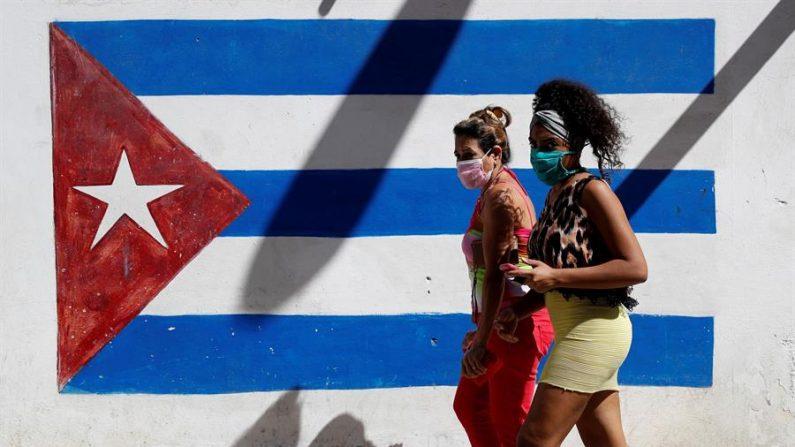 Dos mujeres caminan frente a un graffiti de la bandera cubana, en La Habana (Cuba). EFE/Yander Zamora