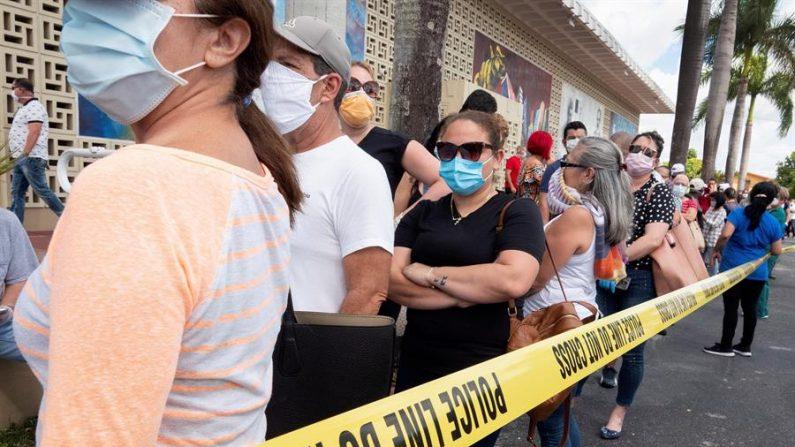 La gente hace cola para recibir la solicitud impresa de los beneficios de desempleo en el estacionamiento de la Biblioteca Kennedy en Hialeah, Florida, el 7 de abril de 2020. EFE/Cristóbal Herrera