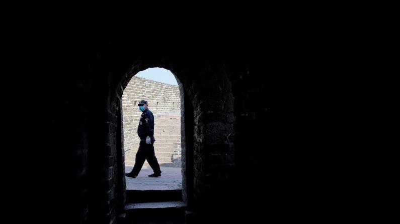 Un guardia de seguridad usa una máscara protectora en la casi vacía Gran Muralla de Badaling en Beijing, China, el 24 de marzo de 2020. (Lintao Zhang/Getty Images)