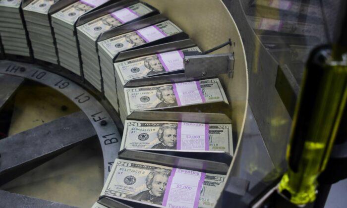 Los paquetes de billetes de 20 dólares recién impresos se procesan para su empaquetado en la Oficina del Tesoro de Grabado e Impresión de EE.UU. en Washington el 20 de julio de 2018. (Eva Hawbach/AFP a través de Getty Images)