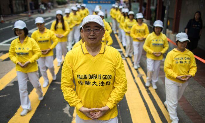 Practicantes de la disciplina espiritual Falun Gong participan en una marcha en Hong Kong, el 27 de abril de 2019. (DALE DE LA REY/AFP a través de Getty Images)