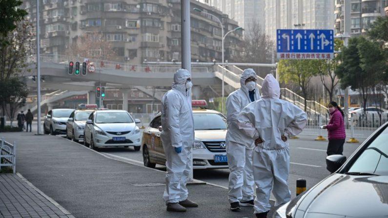 Esta foto tomada el 30 de enero de 2020 muestra a funcionarios con trajes protectores reunidos en una calle después de que un anciano con una máscara facial (no en la foto) se derrumbó y murió en la acera cerca de un hospital en Wuhan. Los periodistas de la AFP vieron el cuerpo el 30 de enero, no mucho antes de que llegara un vehículo de emergencia con policías y personal médico en trajes de protección de cuerpo completo. (HECTOR RETAMAL/ AFP a través de Getty Images)