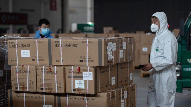 Los miembros del personal y los voluntarios transfieren suministros médicos en un almacén de un centro de exposiciones que se convirtió en un hospital improvisado en Wuhan, China, el 4 de febrero de 2020. (STR/AFP a través de Getty Images)
