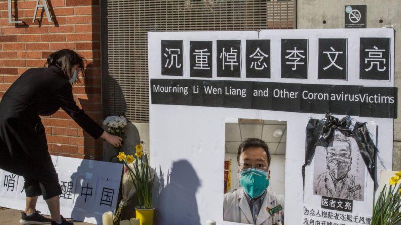 Los estudiantes chinos y sus partidarios sostienen un monumento en memoria del Dr. Li Wenliang, quien fue el denunciante del coronavirus que se originó en Wuhan, China y causó la muerte del doctor en esa ciudad, en las afueras del campus de la UCLA en Westwood, California, el 15 de febrero de 2020. (Mark Ralston/AFP vía Getty Images)