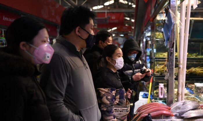 Habitantes de Beijing usan máscaras mientras compran en un mercado el 27 de febrero de 2020. (Greg Baker / AFP a través de Getty Images)