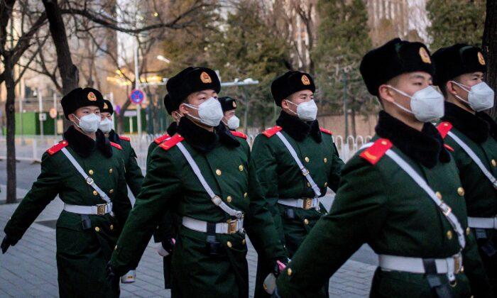 Policías paramilitares con máscaras faciales marchando en una calle de Beijing, el 1 de marzo de 2020. (Nicolas Asfouri/AFP a través de Getty Images)