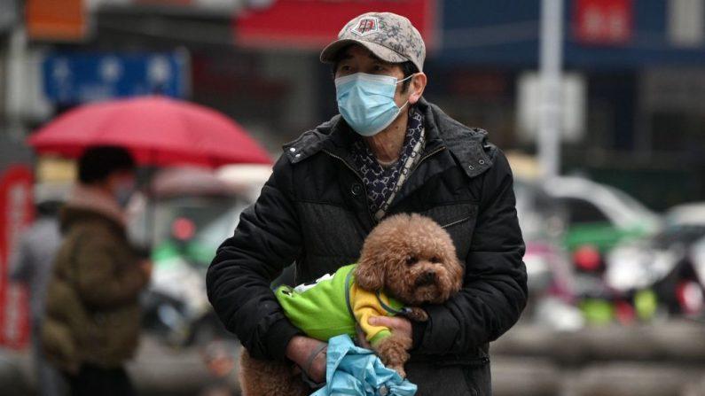 Un hombre con una máscara facial lleva a su perro a lo largo de una calle en Jiujiang en la provincia central de Jiangxi en China el 6 de marzo de 2020. (NOEL CELIS/AFP vía Getty Images)