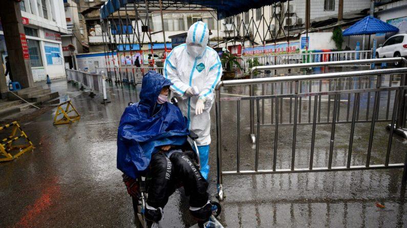 Un trabajador médico ayuda a un hombre que busca tratamiento en una clínica de fiebre en el Hospital Huanggang Zhongxin en Huanggang, en la provincia central de Hubei de China el 27 de marzo de 2020. (Noel Celis/AFP a través de Getty Images)