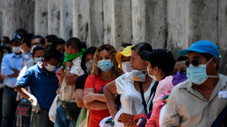 La gente usa máscaras contra la propagación del virus del PCCh mientras hace cola para entrar en un banco de San Salvador (El Salvador) el 30 de marzo de 2020. (YURI CORTEZ/AFP vía Getty Images)