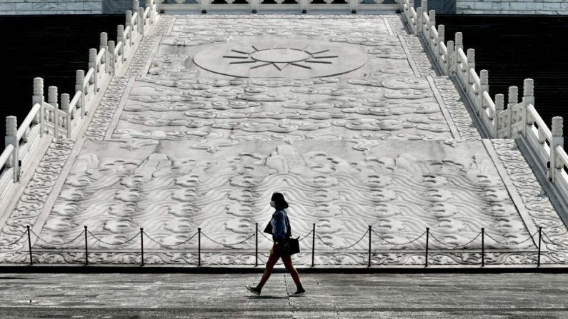 Una mujer con una máscara facial camina frente al Salón Conmemorativo de Chiang Kai-shek en Taipei, Taiwán, el 31 de marzo de 2020. (Sam Yeh/AFP a través de Getty Images)
