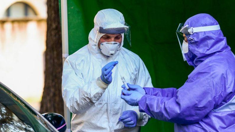 Trabajadores médicos con una máscara facial y un mono realizan pruebas de detección del virus del PCCh en personas que llegan en coche al exterior del policlínico de Alessandria, Piamonte, Italia, el 2 de abril de 2020 durante el cierre del país para frenar la propagación del virus. (MIGUEL MEDINA/AFP vía Getty Images)