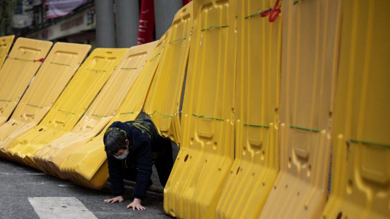 Una mujer mayor se arrastra debajo de una barricada amarilla que separa un complejo residencial en Wuhan, China, el 2 de abril de 2020. (NOEL CELIS/AFP a través de Getty Images)