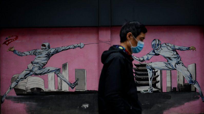 Un hombre con una máscara facial pasa junto a un mural a lo largo de una calle en Wuhan, provincia central de Hubei, China, el 2 de abril de 2020. (NOEL CELIS/AFP a través de Getty Images)