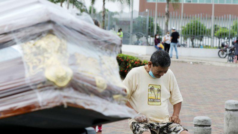 Un pariente de una víctima de coronavirus llora junto al ataúd que está siendo transportado en una camioneta el 4 de abril de 2020 en Guayaquil, Ecuador. (Francisco Macias/Getty Images)