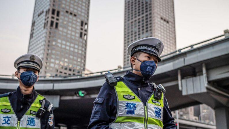 Oficiales de policía con mascarillas patrullan una calle de Beijing el 7 de abril de 2020. (Nicolas Asfouri/AFP vía Getty Images)