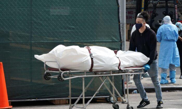 Un cuerpo es trasladado desde un camión de refrigeración que sirve de morgue temporal hasta un vehículo en el Centro Hospitalario Brooklyn, en el barrio de Brooklyn en Nueva York, el 8 de abril de 2020. (Bryan R. SmithAFP via Getty Images)