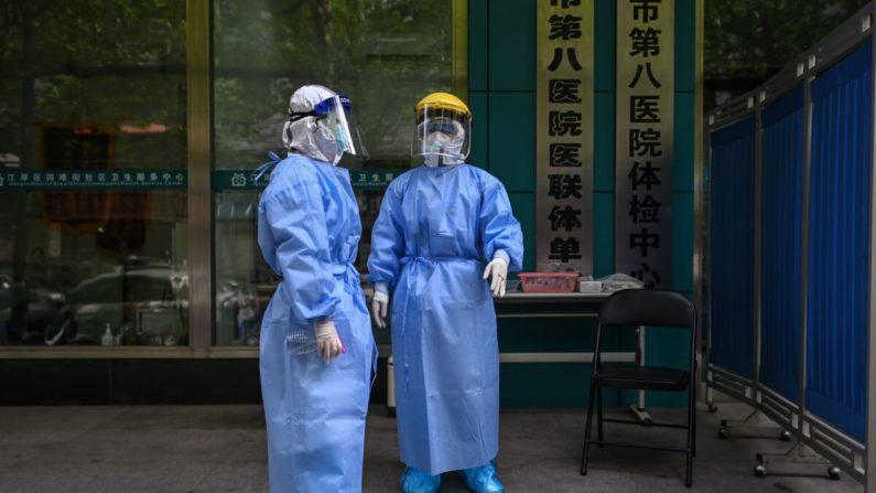 Médicos son vistos mientras toman muestras de hisopado a personas para analizar el nuevo coronavirus COVID-19 en Wuhan, provincia central de Hubei, China, el 16 de abril de 2020. (Héctor Retamal/AFP a través de Getty Images)