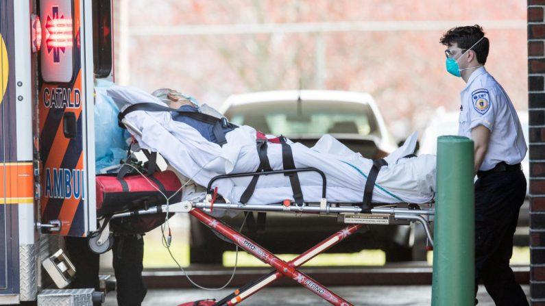 Los socorristas cargan a un paciente en una ambulancia desde un hogar de ancianos donde varias personas contrajeron COVID-19, el 17 de abril de 2020, en Chelsea, Massachusetts. (Scott Eisen/Getty Images)