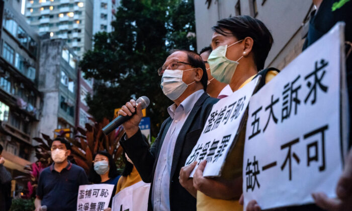 Partidarios de la democracia sostienen pancartas y gritan consignas fuera de la estación de policía del Distrito Oeste, en Hong Kong, el 18 de abril de 2020, después de que, al menos, 14 veteranos y partidarios de la democracia fueron arrestados. (Anthony Kwan/Getty Images)