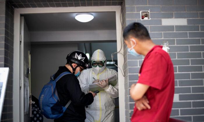 Personas con mascarillas llegan a una clínica para hacerse una prueba de ácido nucleico en Beijing el 29 de abril de 2020. (Noel Celis/AFP vía Getty Images)