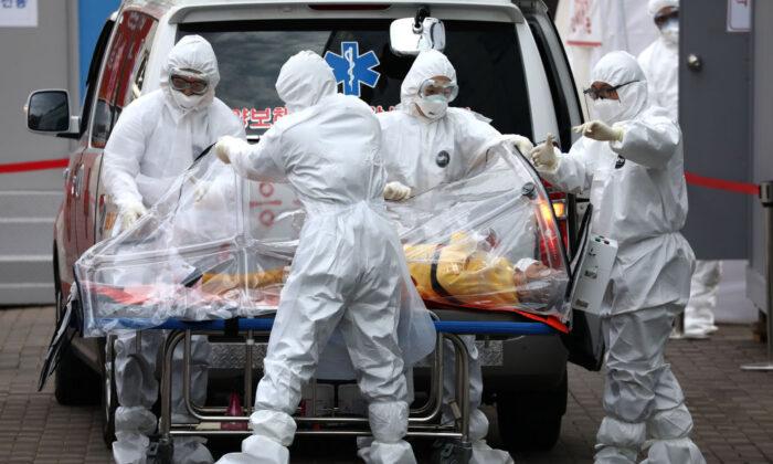 Personal médico con equipo protector, traslada a un paciente infectado con el nuevo coronavirus desde una ambulancia hacia un hospital en Seúl, Corea del Sur, el 9 de marzo de 2020. (Chung Sung-Jun/Getty Images)