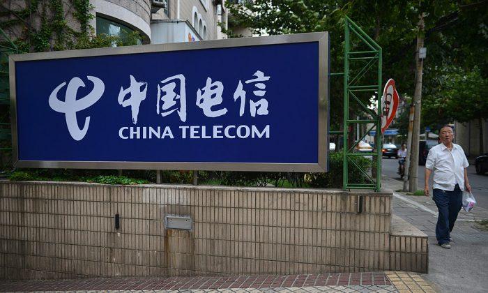 Un peatón pasa por delante de un cartel de China Telecom en una calle de Shanghai el 21 de agosto de 2013. (PETER PARKS/AFP/Getty Images)