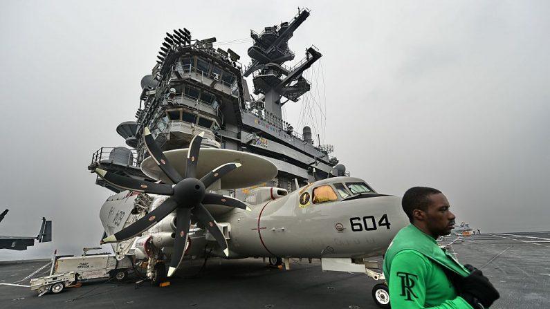 Un miembro de la tripulación está de pie delante de un avión Hawkeyes E-2D en la cubierta de vuelo a bordo del portaaviones USS Theodore Roosevelt (CVN 71) mientras el buque navega hacia el Estrecho de Malaca en dirección a Singapur el 23 de octubre de 2015. (ROSLAN RAHMAN/AFP a través de Getty Images)