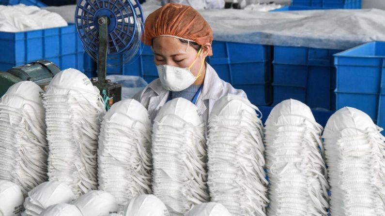 Una trabajadora produce máscaras protectoras en una fábrica en la ciudad de Handan, provincia de Hebei, China, el 28 de febrero de 2020. (STR/AFP a través de Getty Images)