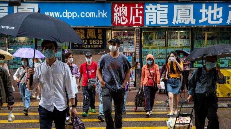 El fundador y CEO de ImpactHK, Jeff Rotmeyer (C), cruza una calle después de repartir suministros de mascarillas faciales, desinfectantes de manos, alimentos y bebidas a los desamparados y personas necesitadas en Hong Kong el 28 de marzo de 2020. (Isaac Lawrence/AFP vía Getty Images)