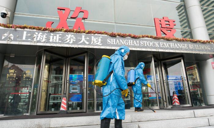 Trabajadores médicos rocían antiséptico fuera de la puerta principal del edificio de la Bolsa de Valores de Shangai el 3 de febrero de 2020. (Yifan Ding/Getty Images)