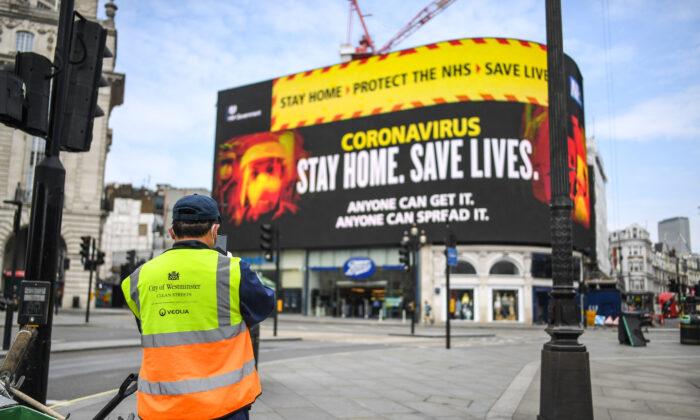 Un limpiador de calles frente a los mensajes del virus del PCCh en Piccadilly Circus en Londres el 8 de abril de 2020. (Peter Summers/Getty Images)